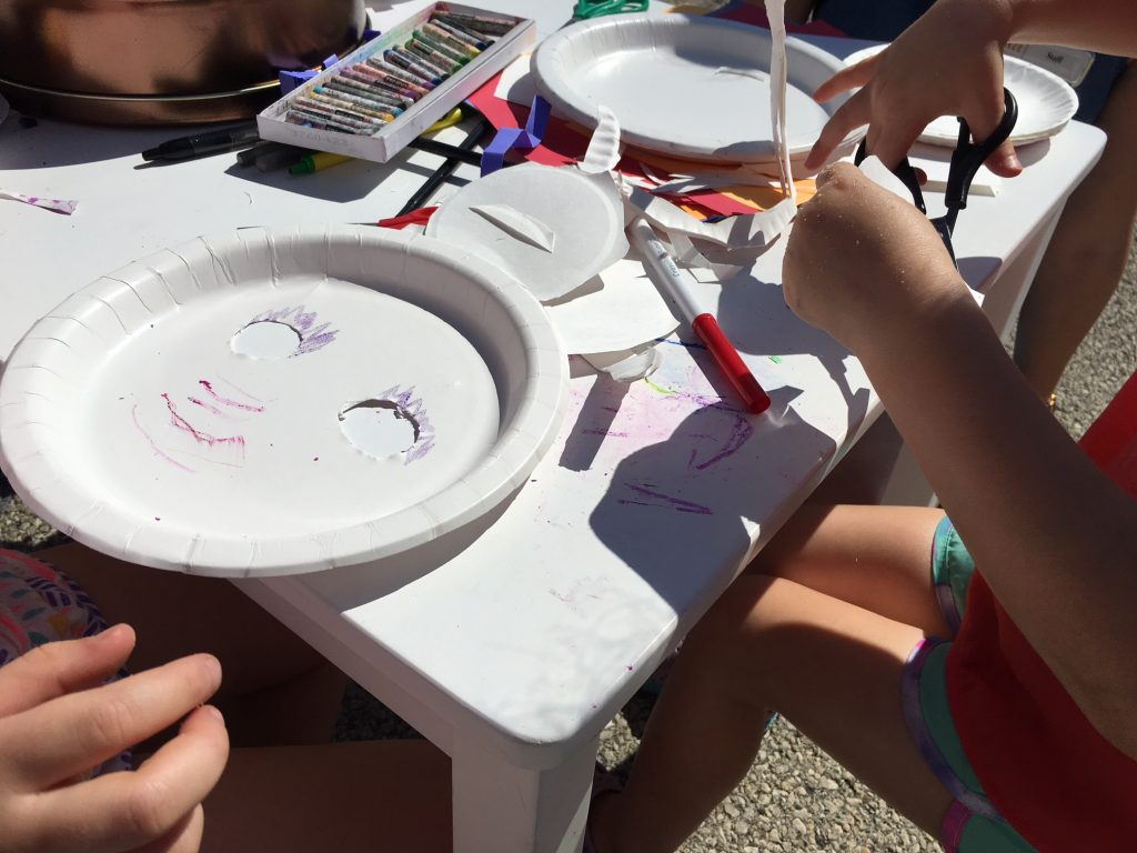 Art supplies and a handmade paper plate mask sit on a white table outside with kids and adults sitting around the table.