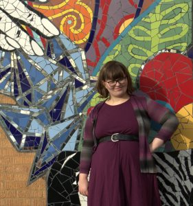 Carolyn standing and smiling in front of a colorful mosaic wall.