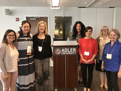 Jenni Rook and Marni Rosen standing with 2018 key note speaker and fellow attendees.