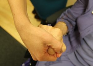 A close up photo of an older woman and younger woman holding hands.