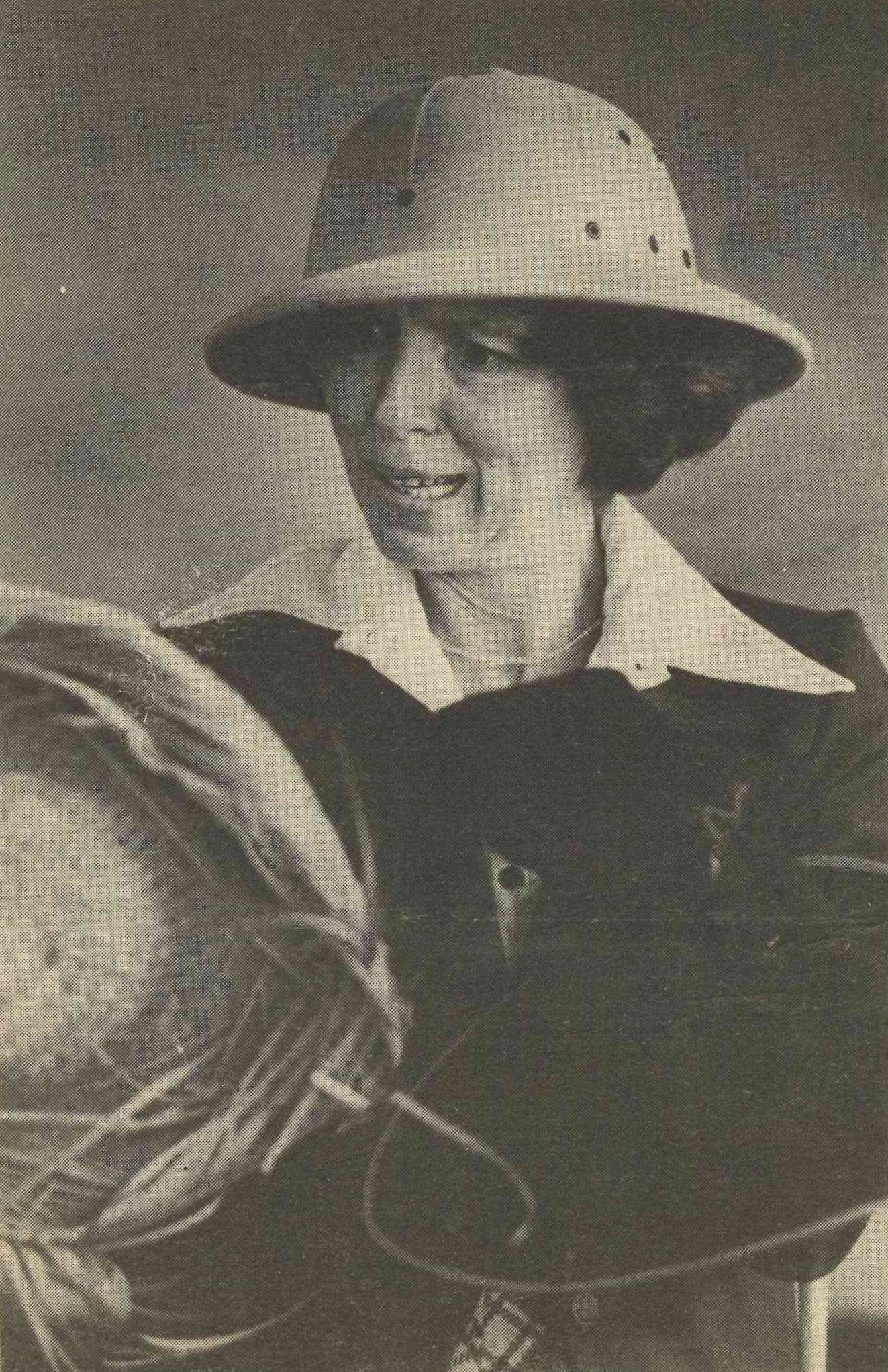 Black and white photo of Toddy wearing an explorer's hat and holding other hats.