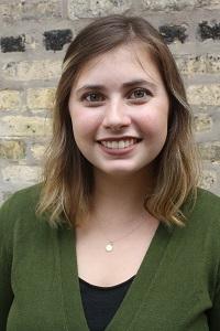 Savannah smiling in front of a brick wall.