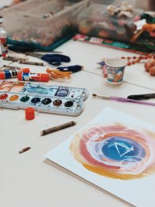 Colorful watercolors, pencils, crayons, glue, and additional art supplies scattered on a table.